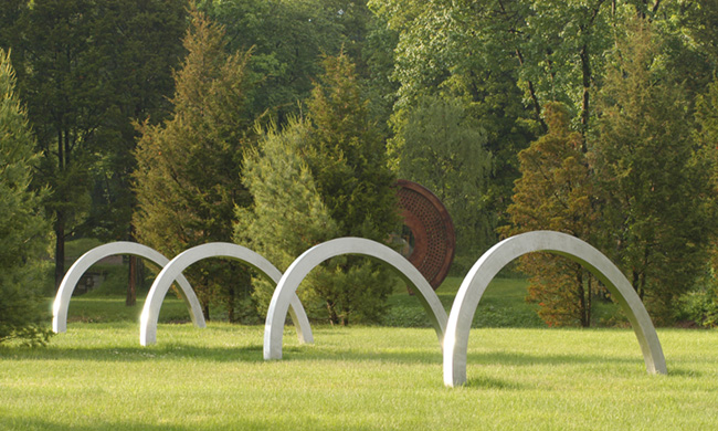 Edward Tufte, Spring Arcs, 2002-2004, installed 2004. 4 stainless steel arcs, tilted 12 degrees from the vertical, 6 feet high, base parallelogram 12 by 67 feet, solid stainless steel, weight 12,800 pounds.