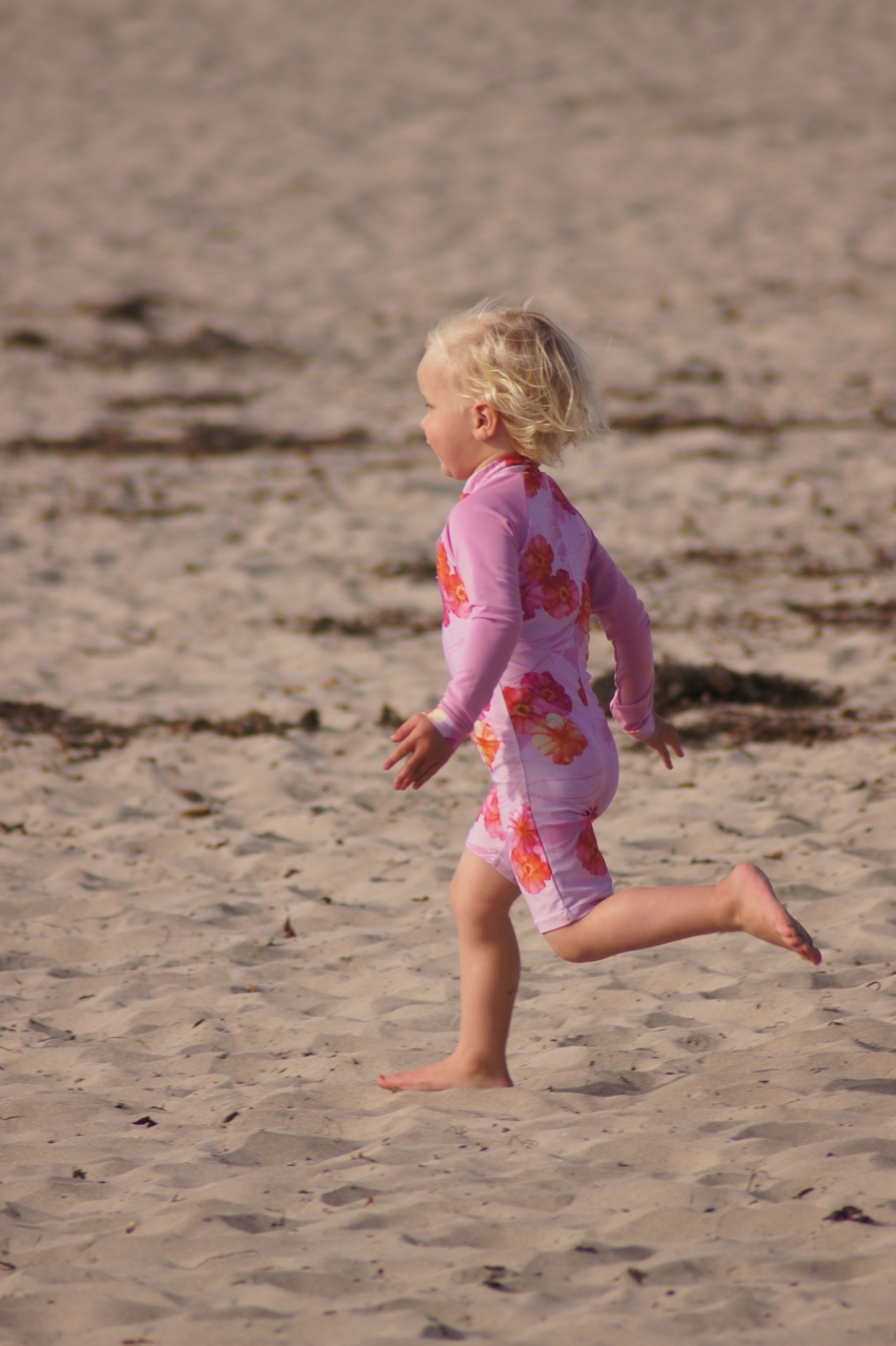 Little girl joyously running across the beach