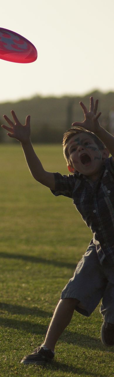 Photo of a kid catching a frisbee. He's putting everything he's got into it.